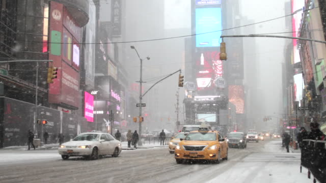 a bizzard scene with traffic in times square new york. - snow storm stock videos and b-roll footage
