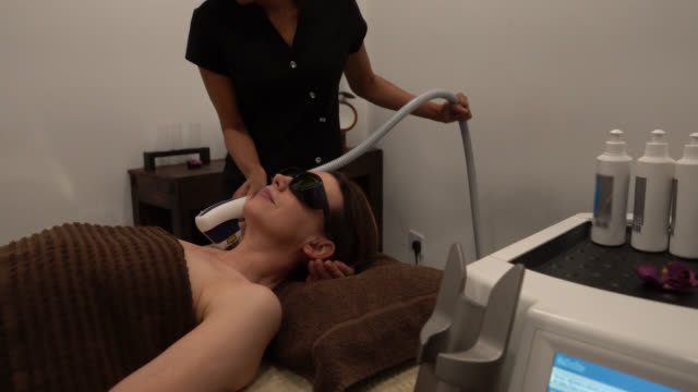 black aesthetician doing a laser treatment to female customer on armpit with laser at the spa - armpit stock videos and b-roll footage