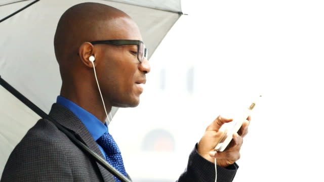 Black African bald businessman taking on mobile phone using miked in-ear headphones