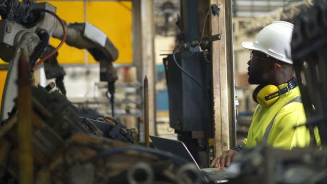 4k black african engineer working on industrial robots - 4k stock videos & royalty-free footage