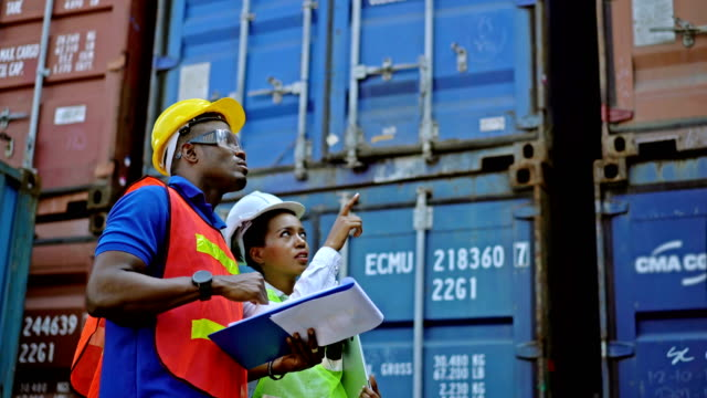 vidéos et rushes de 4k black african engineers holding clipboard checking shipping cargo freights in front of cargo containers in shipping container yard 4k black african engineers holding clipboard checking shipping cargo freights in front of cargo containers in shipping con - port de commerce