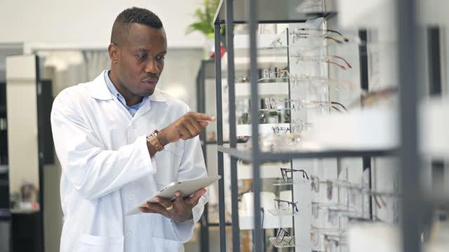 black african optometrist using digital tablet checking eyeglasses on the shelf - lens optical instrument stock videos & royalty-free footage