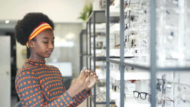 4k black african teenage girl trying on eyeglasses in optical store - lens optical instrument stock videos & royalty-free footage
