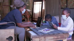 Black African woman using a laptop and digital tablet to home school her two young children at their dilapidated home during lockdown for Covid-19 Coronavirus pandemic, South Africa