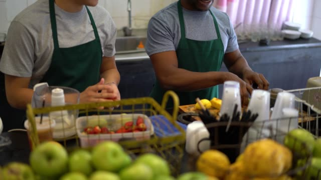 Black and asian salesman working at a juice bar working as a team, one choosing the fruits and the other chopping and adding them into the blender