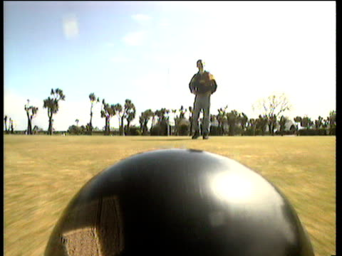 black and red lawn bowling ball races down the green man bowls another bowl black and red ball settles against the jack uk - bowl stock videos & royalty-free footage