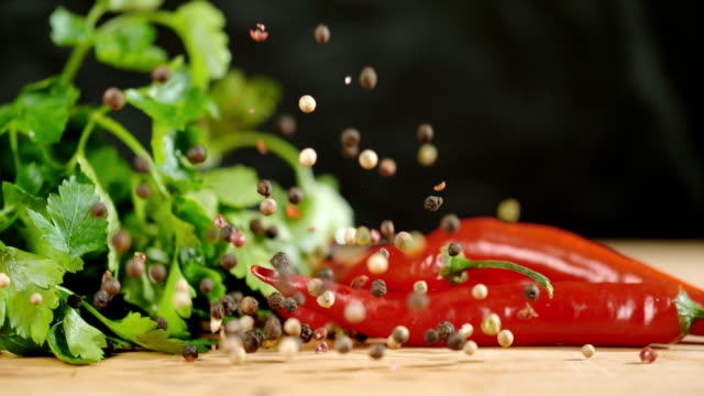 slo mo black and while peppercorns falling on vegetables - parsley stock videos and b-roll footage