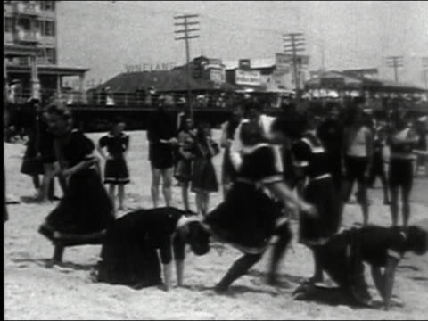 black and white 1903 wide shot women running and playing leap frog game on beach / cameraman filming them - hoppa bock bildbanksvideor och videomaterial från bakom kulisserna
