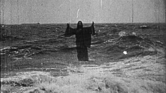 vídeos de stock e filmes b-roll de black and white 1914 composite wide shot jesus rising from water and walking on surface / praying as waves crash - milagres