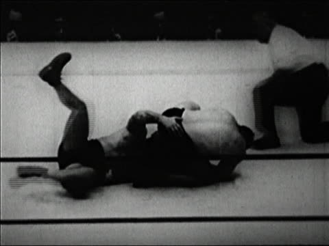 black and white 1920s b/w medium shot ed lewis breaking out of hold by kicking gus sonnenberg / referee counting / audio - ガス ソネンバーグ点の映像素材/bロール
