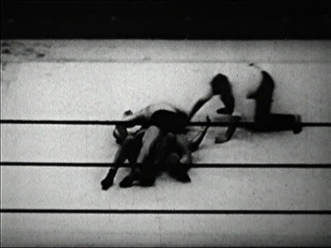 black and white 1920s medium shot wrestling / ed lewis and g sonnenberg in headlock / trainers handling wrestlers / audio - tackling stock videos & royalty-free footage