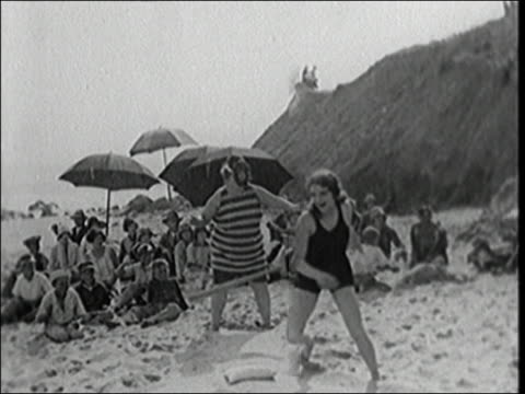 stockvideo's en b-roll-footage met black and white 1927 slow motion women playing softball game on beach / batter swinging and running bases - 20 29 jaar