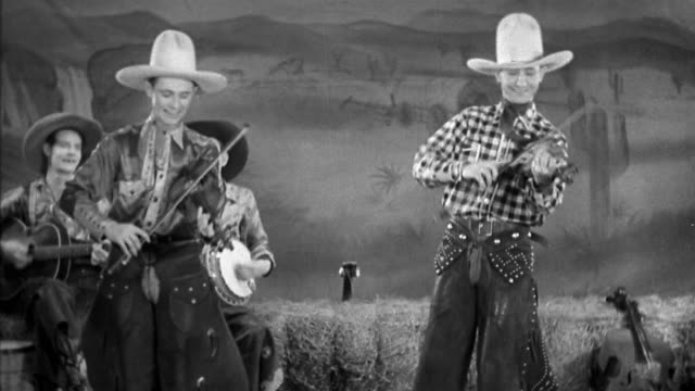black and white 1930 medium shot two cowboys doing tricks while playing fiddles - violin stock videos & royalty-free footage