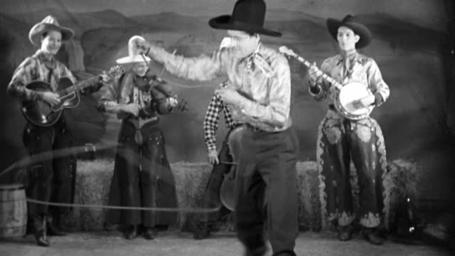 black and white 1930 wide shot cowboy performing rope trick with band in background - cowboy stock videos & royalty-free footage
