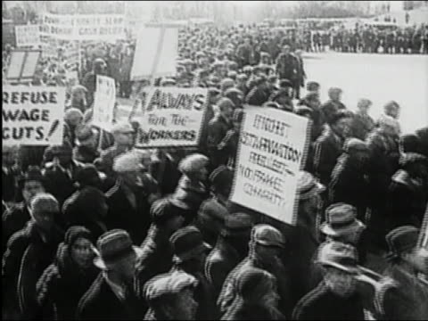 black and white 1930s high angle pan crowd at great depression labor rally holding placards and marching / audio - la grande depressione video stock e b–roll