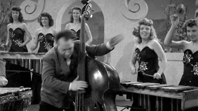 black and white 1930s medium shot energetic man playing double bass with female band members playing marimbas in background - black and white stock videos & royalty-free footage