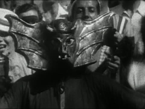 Black and white 1930s person in bat/devil mask dancing / AUDIO / South America