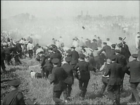 vidéos et rushes de black and white 1930s wide shot police officers chasing and beating up strikers / audio / pittsburgh, pennsylvania - la grande dépression