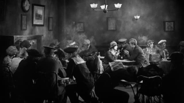 vídeos de stock e filmes b-roll de black and white 1930s wide shot women and men sitting in a smoky wwi-era cafe/ couples getting up and dancing - fumar