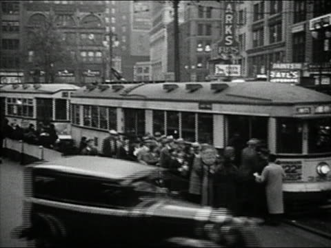 black and white 1932 high angle wide shot pan lines of riders boarding trolley car on busy street / detroit, michigan - tram stock videos & royalty-free footage