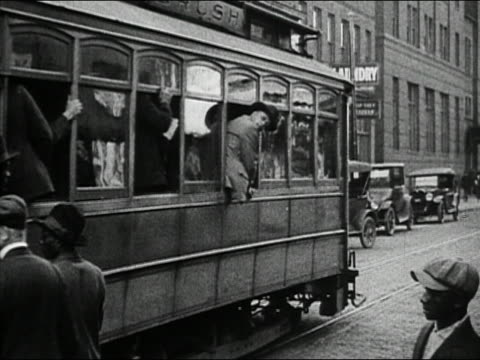 Black and white 1932 people riding and hanging onto the back of trolley car / Detroit