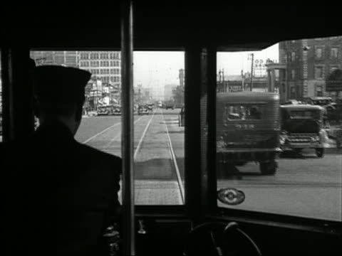 Black and white 1932 point of view over the shoulder of trolley driver drving through streets of Detroit, Michigan
