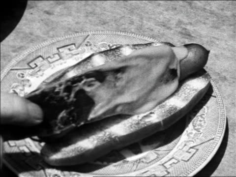 black and white 1940 close up spatula spreads mustard on hot dog and hand picks it up / coney island, ny / industrial - hot dog stock videos & royalty-free footage