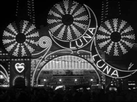 Black and white 1940 Luna Park lights and signs with people in foreground at night / Coney Island, NY / industrial /AUDIO