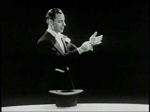 vídeos de stock, filmes e b-roll de black and white 1940 magician performing trick w/egg and pulls a bird out of a top hat / bird flies away / audio - mágico