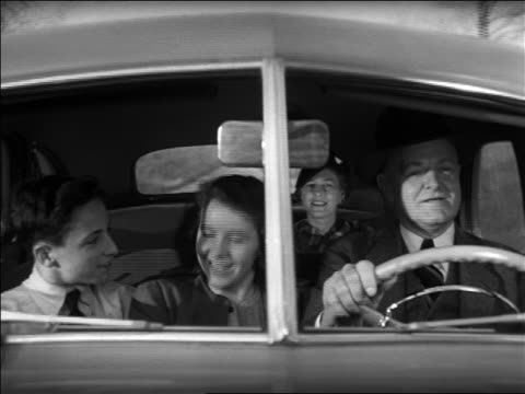 black and white 1940 man driving car with 2 children in front seat and woman in back seat / industrial /audio - クラシックカー点の映像素材/bロール