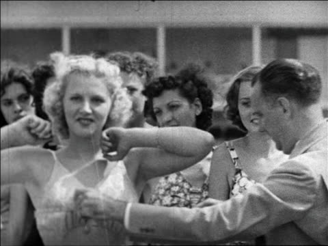 Black and white 1940 man measures woman's bust with measuring tape / swimsuit contest / Coney Island, NY /AUDIO