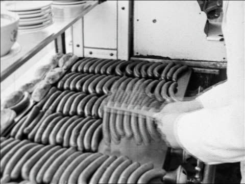 black and white 1940 man's hands flipping rows of hot dogs on griddle / coney island, ny / industrial /audio - hot dog stock videos & royalty-free footage
