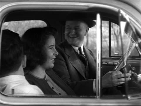 Black and white 1940 middle aged man, teen girl and boy in front seat of car / man talks, girl turns around /AUDIO