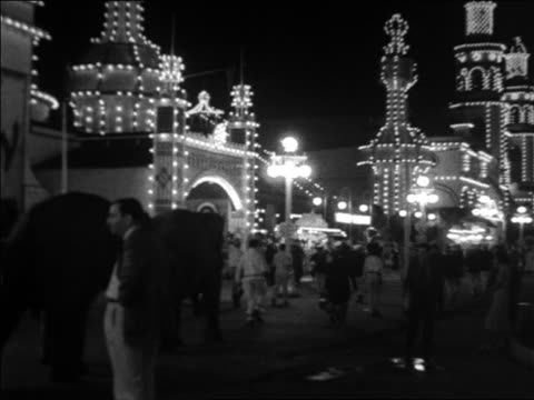 vidéos et rushes de black and white 1940 people and elephants walking at lit coney island at night / industrial /audio - petit groupe d'animaux