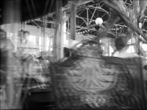 black and white 1940 people riding carousel past camera / coney island, ny / industrial /audio - around the fair n.y stock videos & royalty-free footage