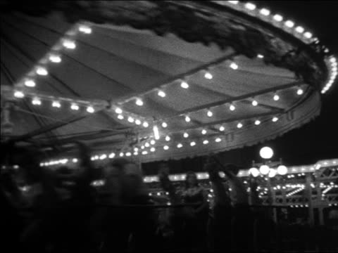 black and white 1940 people riding lit carousel at night / coney island, ny / industrial /audio - 1940 stock-videos und b-roll-filmmaterial