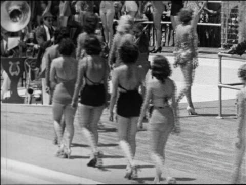 Black and white 1940 rear view line of women in swimsuit contest walking on boardwalk / Coney Island, NY /AUDIO