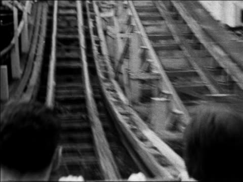 Black and white 1940 roller coaster point of view starting up hill / people's heads in foreground / Coney Island, NY /AUDIO