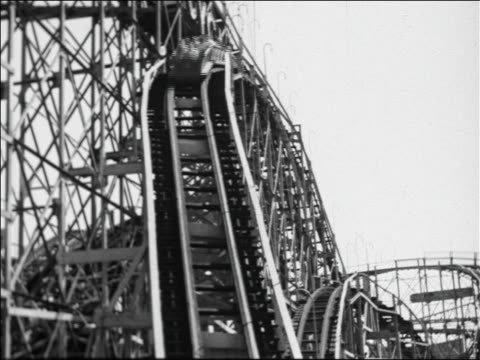 Black and white 1940 roller coaster speeding down hill / Coney Island, NY / industrial /AUDIO