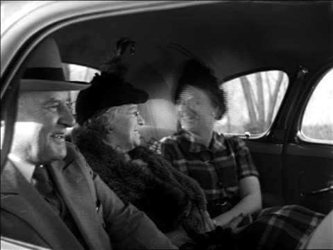 vidéos et rushes de black and white 1940 senior couple and middle aged woman sit in back seat of car smiling + talking / industrial - homme dans un groupe de femmes