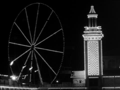 vídeos de stock, filmes e b-roll de black and white 1940 spinning lit ferris wheel and tower at night / coney island, ny / industrial /audio - roda gigante