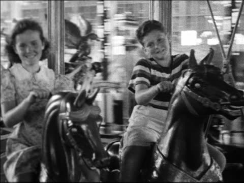 Black and white 1940 tracking shot boy and girl riding horses on carousel / Coney Island, NY / industrial /AUDIO