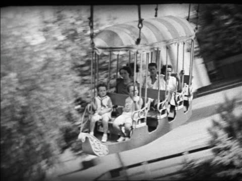 Black and white 1940 tracking shot people on flying spinning amusement park ride / Coney Island, NY / indust /AUDIO