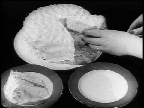 Black and white 1940s close up hands of woman cutting cake and putting slices on dishes / newsreel /AUDIO