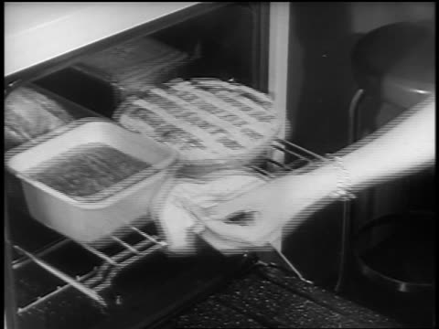 vídeos de stock, filmes e b-roll de black and white 1940s close up hands of woman taking rack of food out of oven / newsreel /audio - fogão