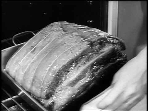 vídeos de stock, filmes e b-roll de black and white 1940s close up hands of woman taking roast meat out of oven / newsreel /audio - fogão
