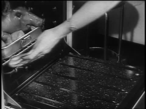 vídeos de stock, filmes e b-roll de black and white 1940s close up hands of woman taking roasted suckling pig out of oven / newsreel /audio - fogão