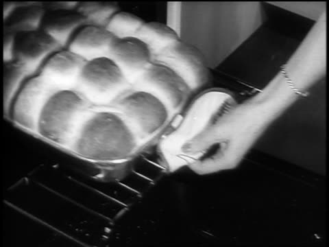 black and white 1940s close up hands of woman taking tray of rolls out of oven / newsreel /audio - black and white stock videos & royalty-free footage