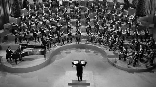 black and white 1940s high angle wide shot energetic conductor leading orchestra - orchestra stock videos & royalty-free footage
