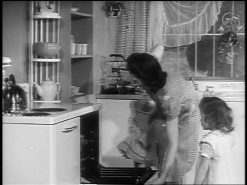 Black and white 1940s housewife taking cakes out of oven as small daughters look on / newsreel /AUDIO